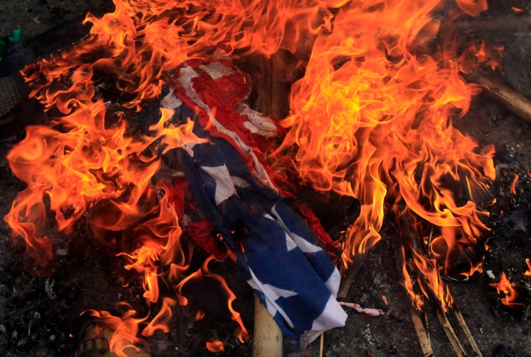 A burning U.S. flag is seen on the ground after it was set on fire by Bangladeshi Muslims during a protest in Dhaka